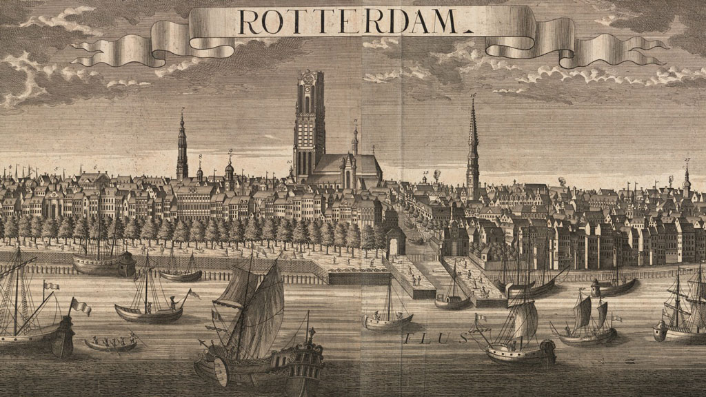 """Black and white print from an engraving depicting a number of differently rigged sailing ships in a river. In background is a town with many small buildings and a few steeples pointing into the sky. In center is one larger cathedral with a square gothic style bell tower rather than a steeple. on a ribbon in the sky at the center reads """"Rotterdam""""."""