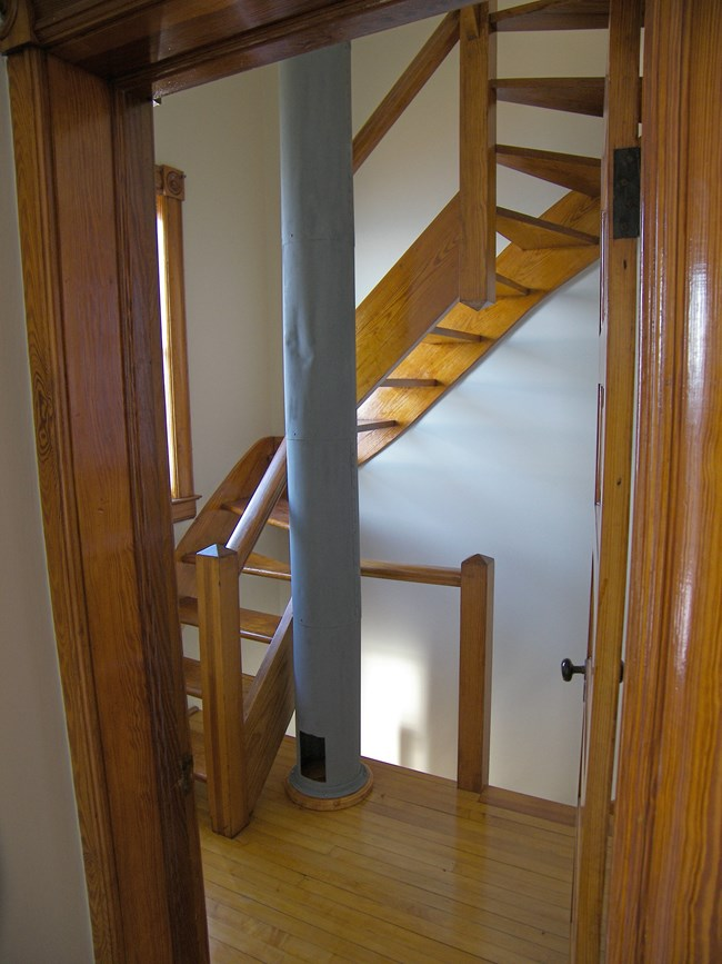 A door open to a wooden staircase and grey tube in the center.
