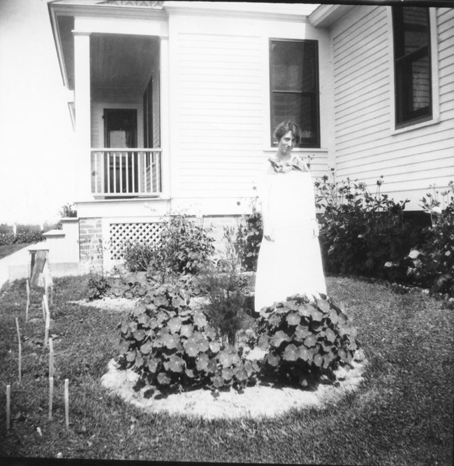 A black and white photo of a woman in a white dress standing in front of flowers.