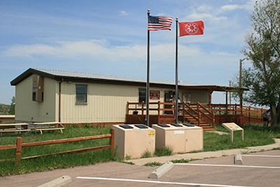 Front view of the White River Visitor Center with Oglala Lakota and USA flags flying