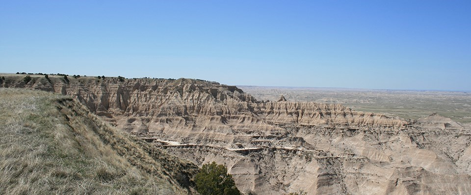 badlands buttes create a high wall, below which prairie spreads out in every direction