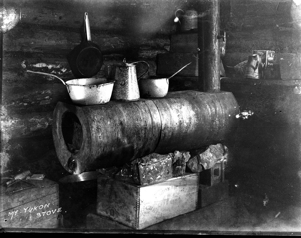 A makeshift kitchen with cooking pots and a coffee pot sitting on a stovepipe stove.