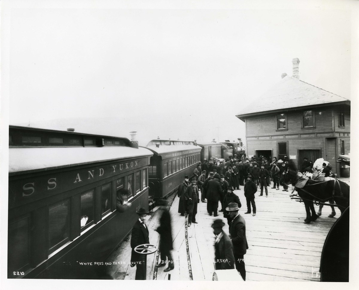 a trail rolling past a station with men standing outside