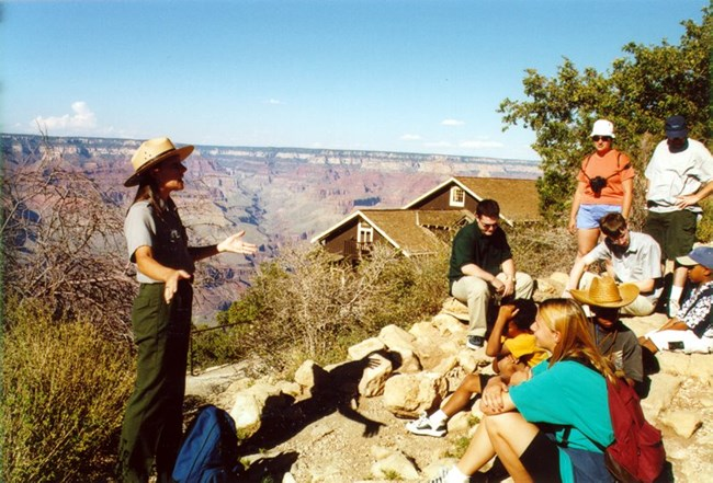 A ranger gives a talk to several visitors in front of Grand Canyon.