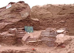 Excavation of a wall in red rock.
