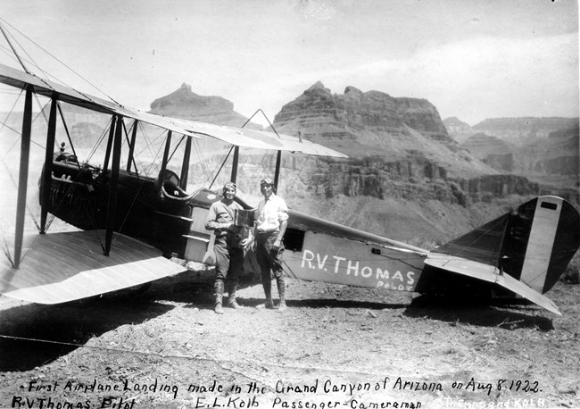 Two pilots standing next to a biplane.