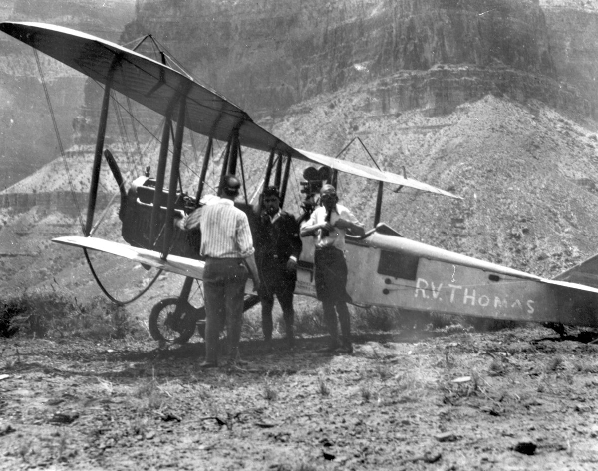 Three people standing next to a biplane.