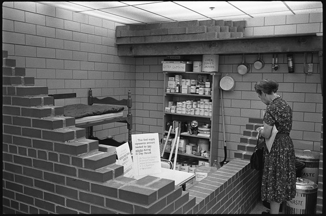 Woman views bomb shelter display which is stocked with food and other supplies