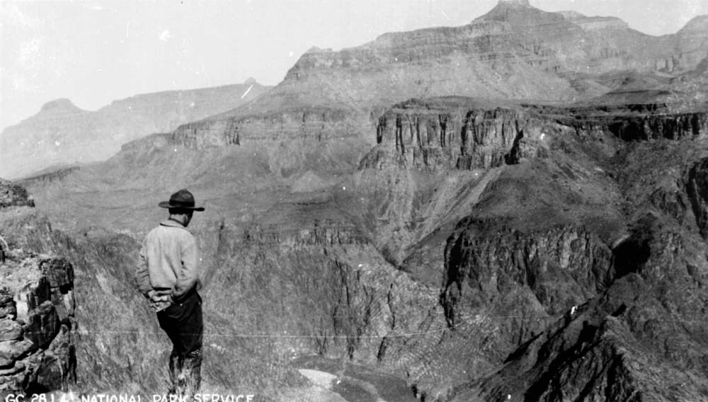 Man in a wide-brimmed facing Grand Canyon's landscape.