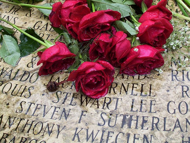 Red roses lie on names engraved in stone at the AIDS Memorial