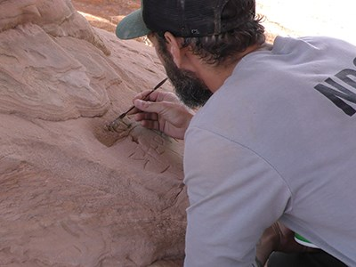 a ranger uses a small tool to press filling into carved graffiti