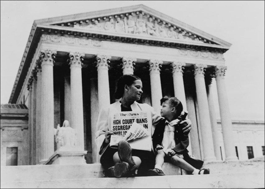 "A black woman and girl sitting on the steps of a large building with Greco-roman columns. The woman holds a newspaper with the headline, ""High Court Bans Segregation."""