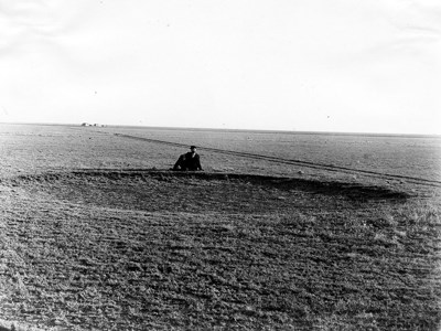 A black and white photo of a man sitting behind a giant hole in the prairie left by a bison wallow