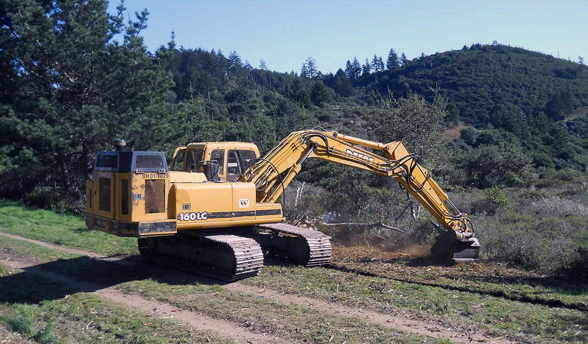 An excavator digs off the side of a dirt road/trail