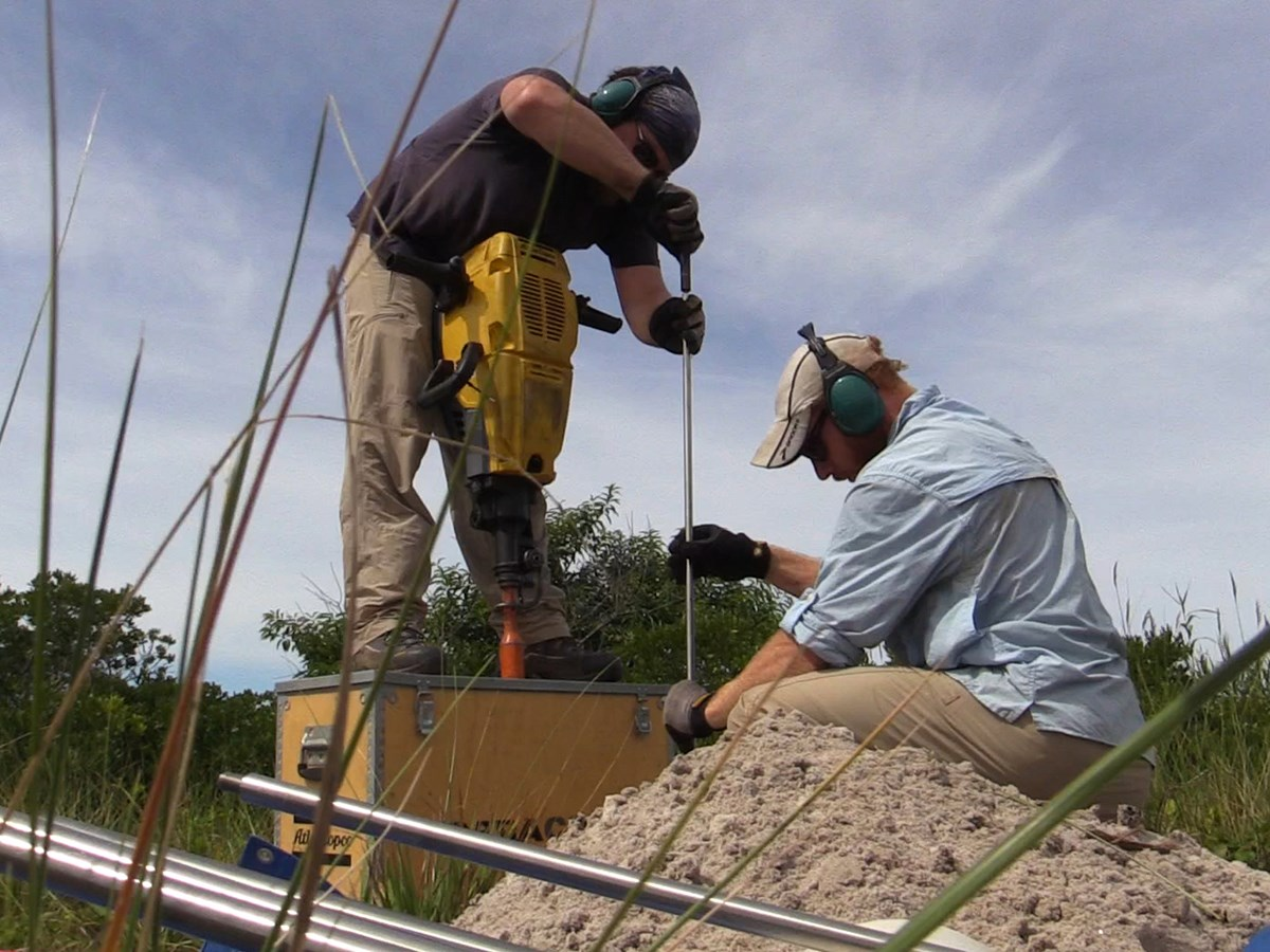 Two men use tools to install elevation markers in sandy soil.