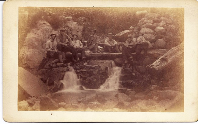 Eight men in a sepia-toned photo from the 1880s seated around a small waterfall.