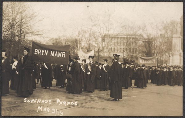 "Postcard image of women in caps and gowns in street. Banners read ""Bryn Mawr"" and ""Wellesley."""