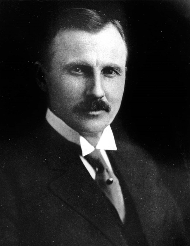 Bust-up portrait of a man in a dark suit and mustache.