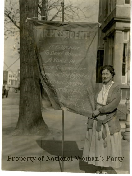 "Mrs. Bartlet carring a ""Mr President"" banner. She stands in front of a building next to the banner holding its pole and the corner."