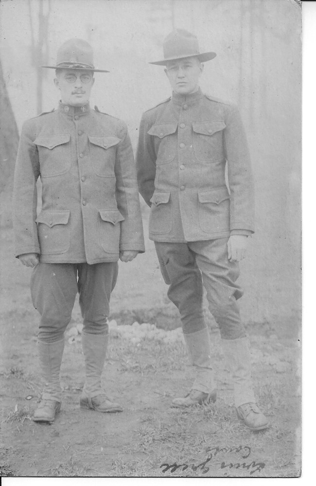 Black and white photograph of two men wearing World War I Army uniforms.