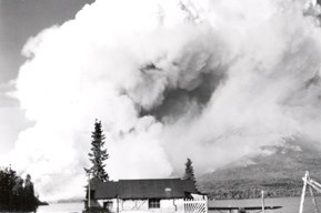 A black and white photograph of smoke from a wildfire behind a home
