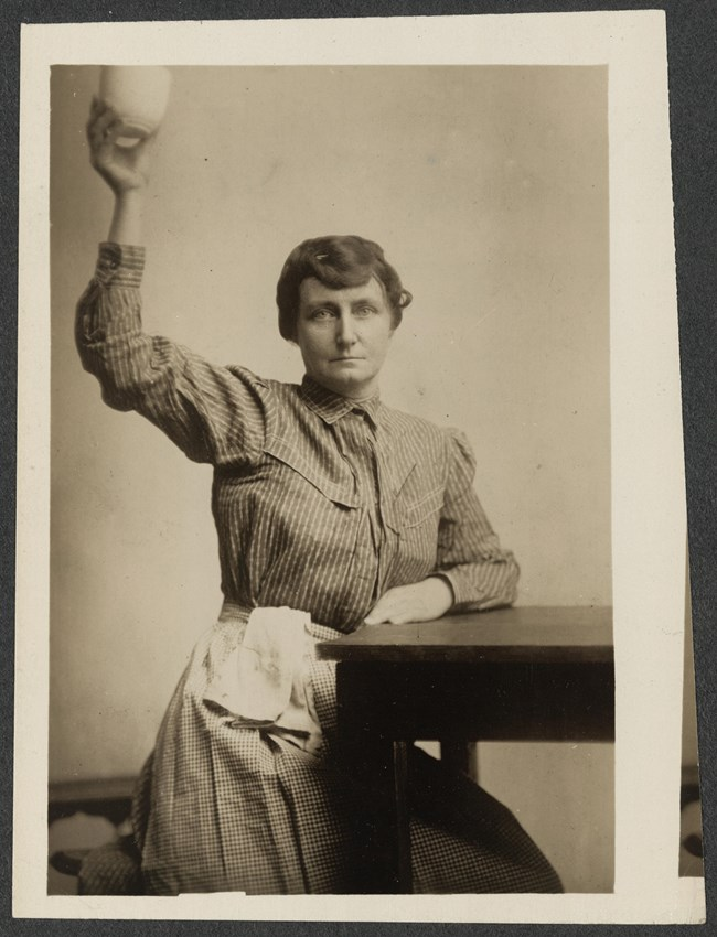 Woman wearing a prison uniform, seated with one arm raised holding a cup.