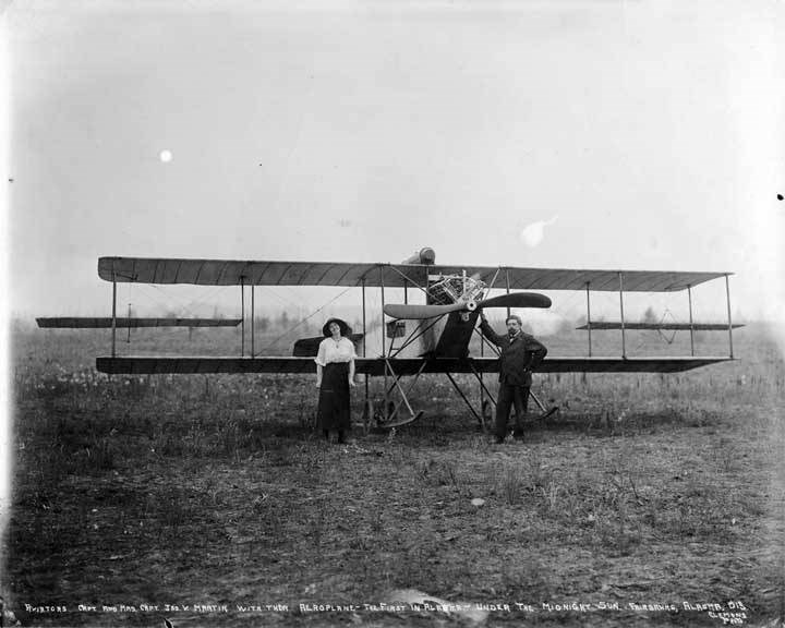 two people standing in front of airplane on ground