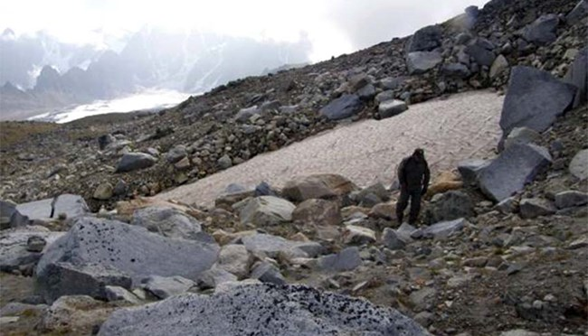 Man walking on rocky hillside by patch of snow