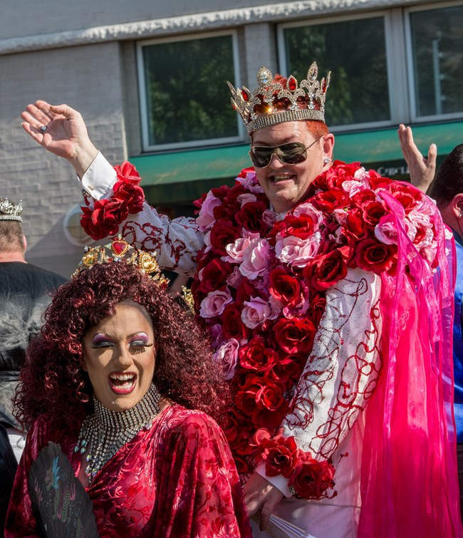 Two people in royal regalia wave to the crowd