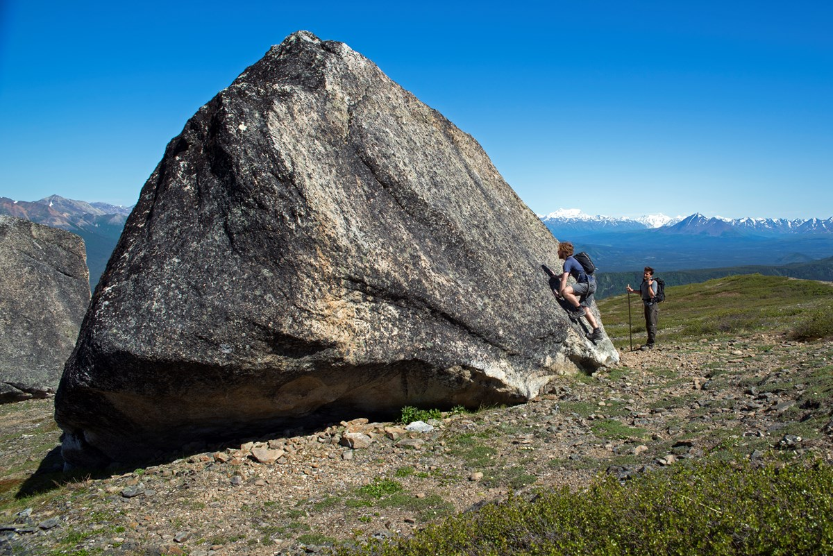 people standing next to an enormous, house-sized boulder