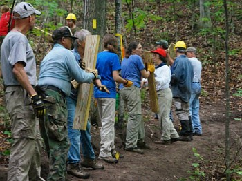 Group of trail workers carrying equipment