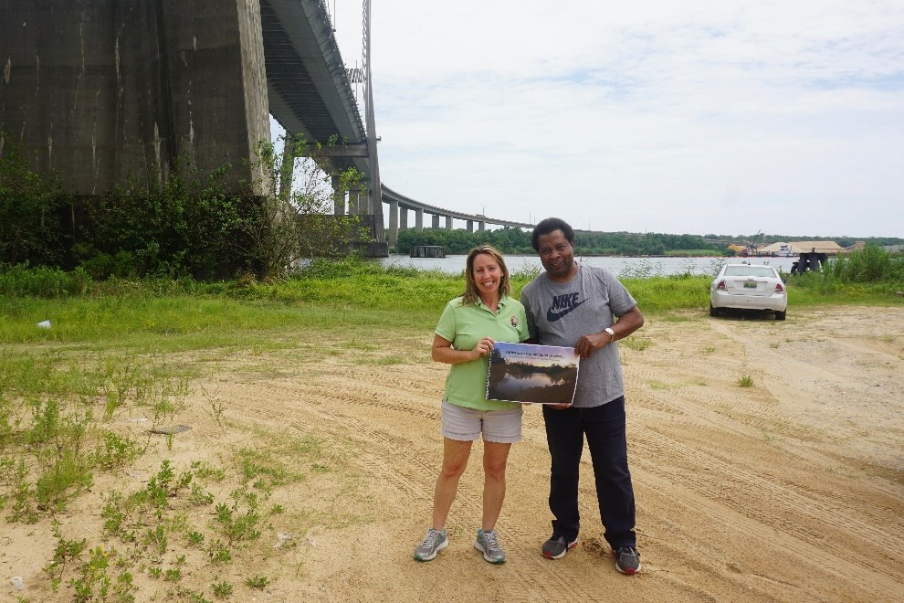 Smith-Incer and Womack hold the Mississippi State University concept plan under the Cochrane Africatown USA Bridge, where the Clotilda first landed. Photo by Margaret Gach, National Park Service.