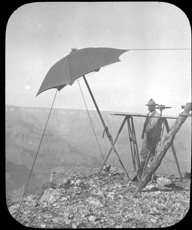 A pioneer stands next to an umbrella-shaped structure on the rim.
