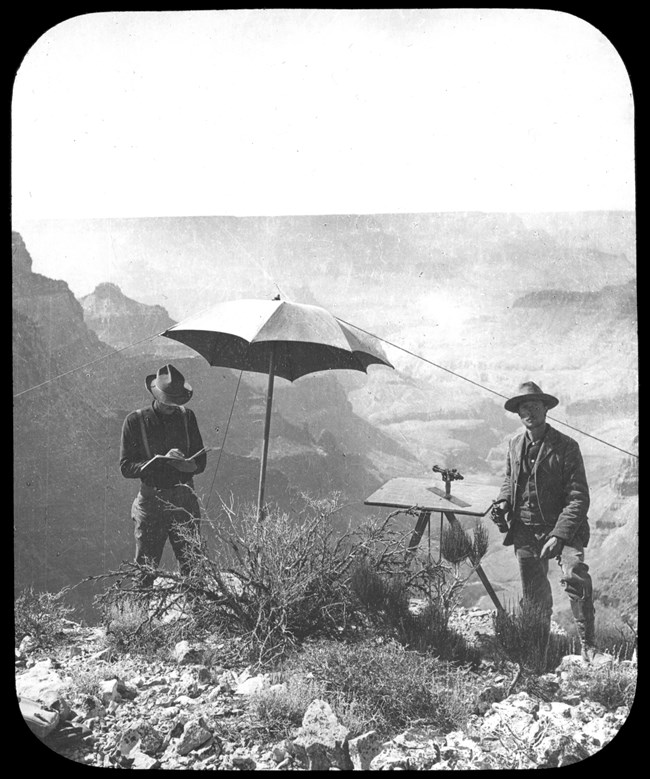 Two men standing with a navigation device and an umbrella between them. Grand Canyon backdrop.