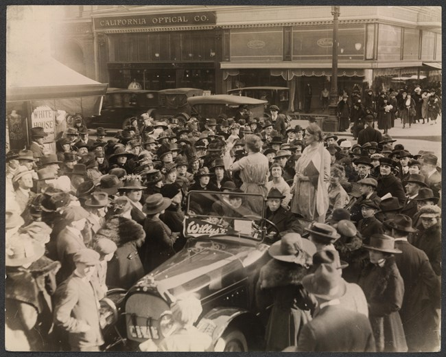 A crowd of people surround a car; two of the women in it are standing and one is speaking.