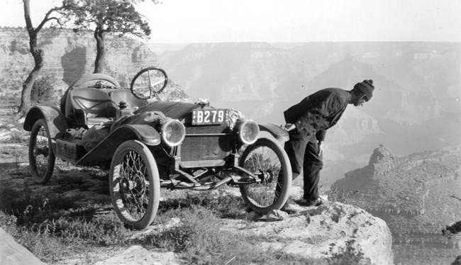 Driver stands next to his car and peers over the edge of the canyon.