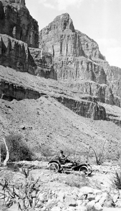 Metz drives along rugged terrain at the base of large canyon cliffs.