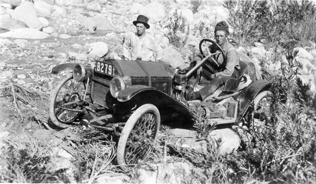 Car among rocks and shrubs with two people inside.