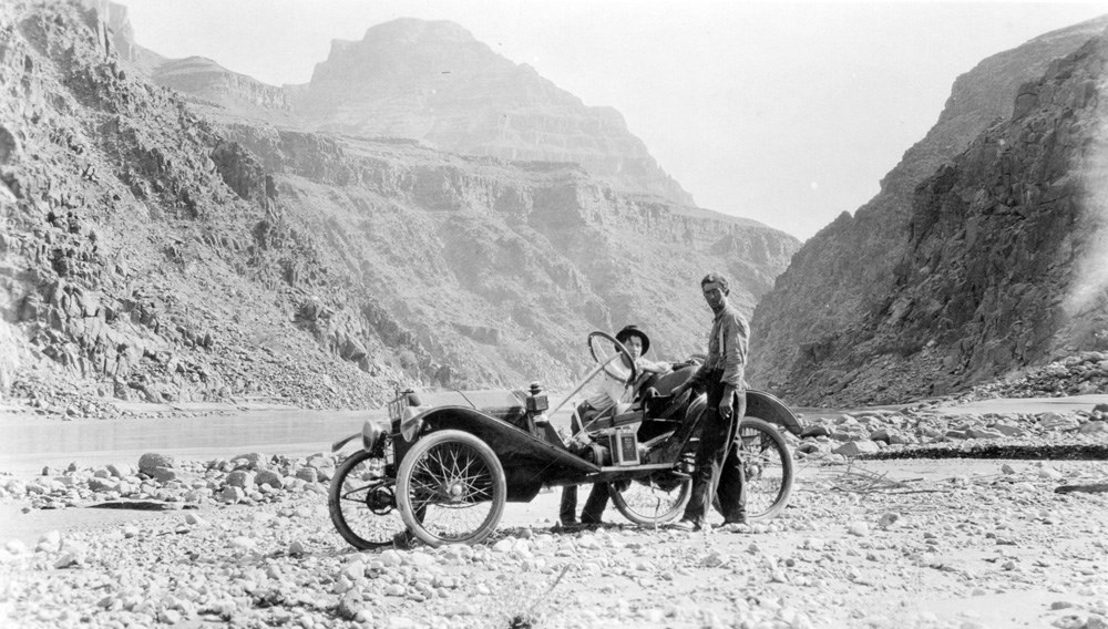 Car and its two drivers on a stretch of flat land inside of Grand Canyon.
