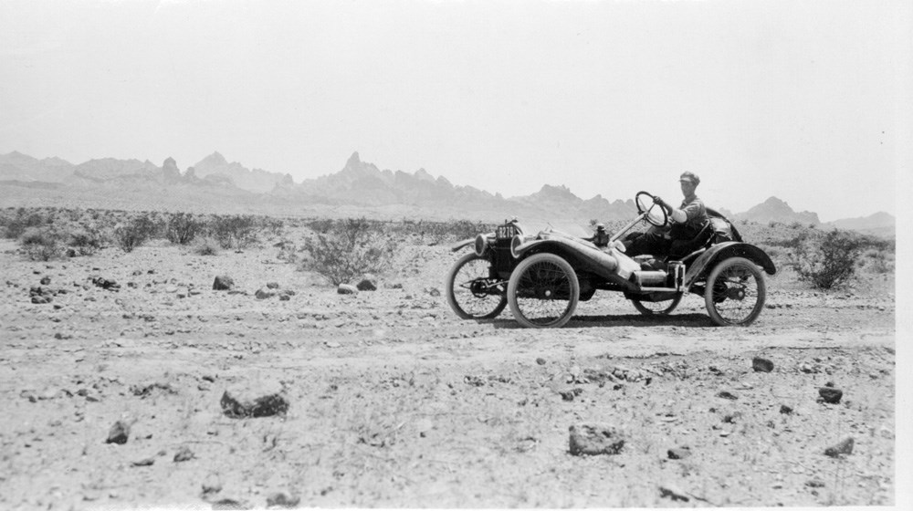 Driver operates car along a flat desert road. Rock formations can be seen in the distance.