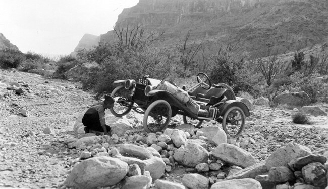 Metz on a section of rocky ground, with driver inspecting a wheel that is tilted up.