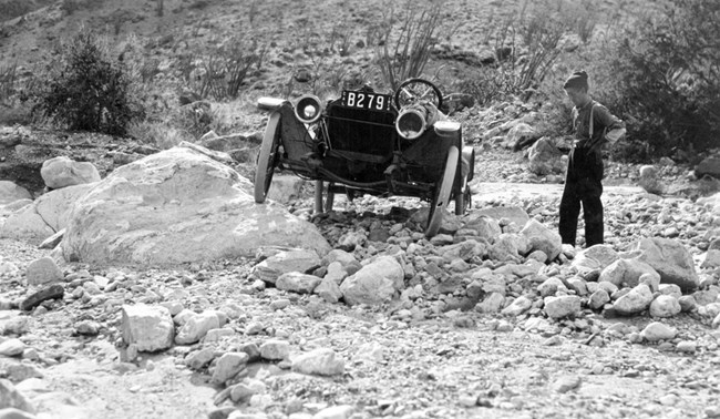 Car stands on a rock pile at an uneven angle, facing front, while the driver stands to the side.