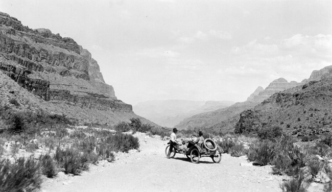 Metz car on a sandy, scrubby road between two large rocky cliffs.