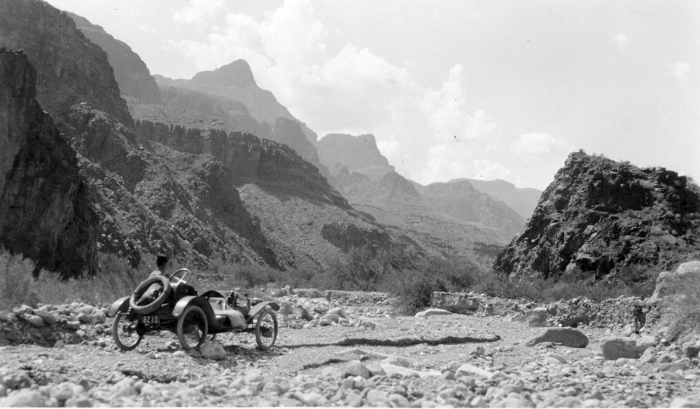 Old fashioned car faces a vast, rugged landscape.