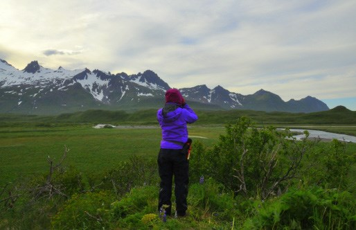 A woman looks out towards a green field and glacier