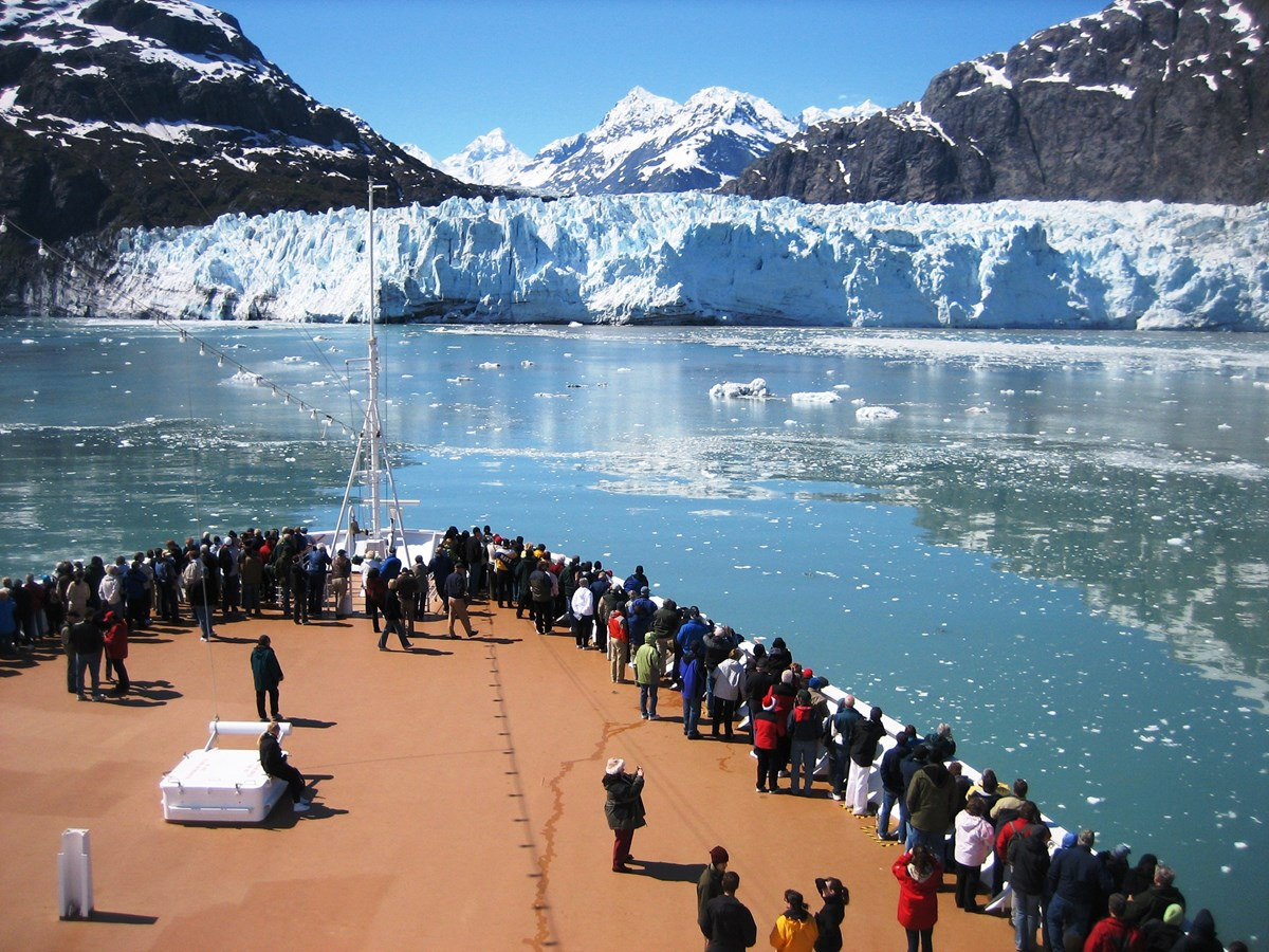Visitors to Glacier bay national park gather at the bow of a cruise ship, overlooking the water