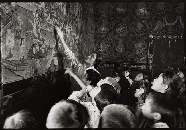 Teacher  pointing to wall mural in front of group of children, Library of Congress, https://www.loc.gov/item/2011646958/