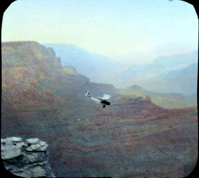 Old fashioned airplane flying above Grand Canyon.