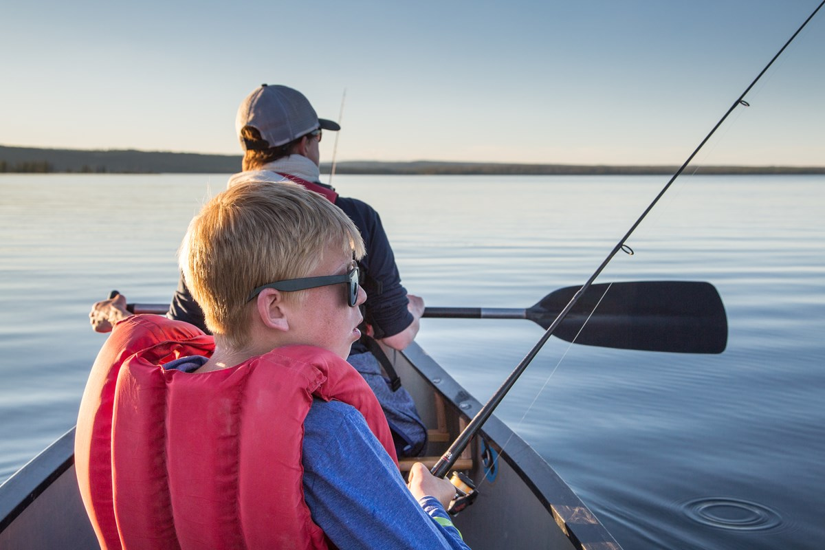 A young boy wearing a personal flotation device is holding a spin fishing rod in a canoe on a lake.