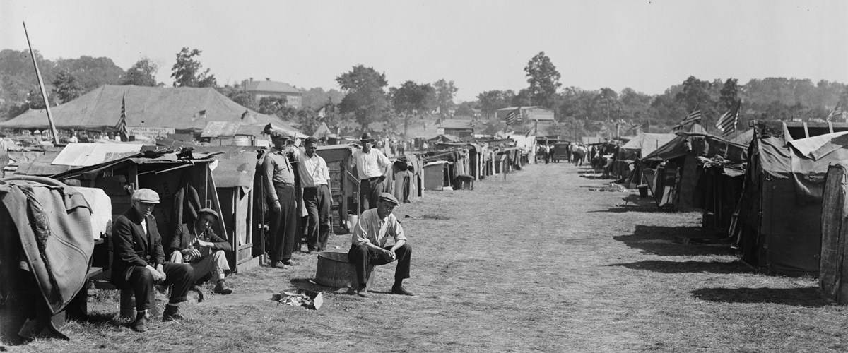 Men sit in front of a row of shanties.
